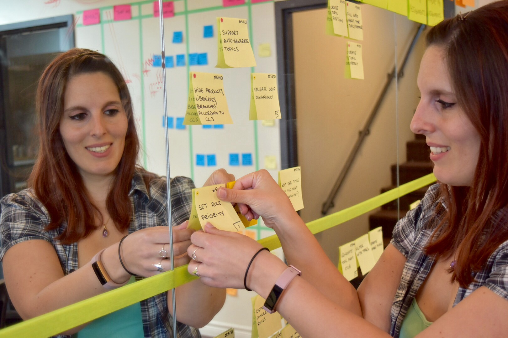 Woman gluing post-it note to mirror