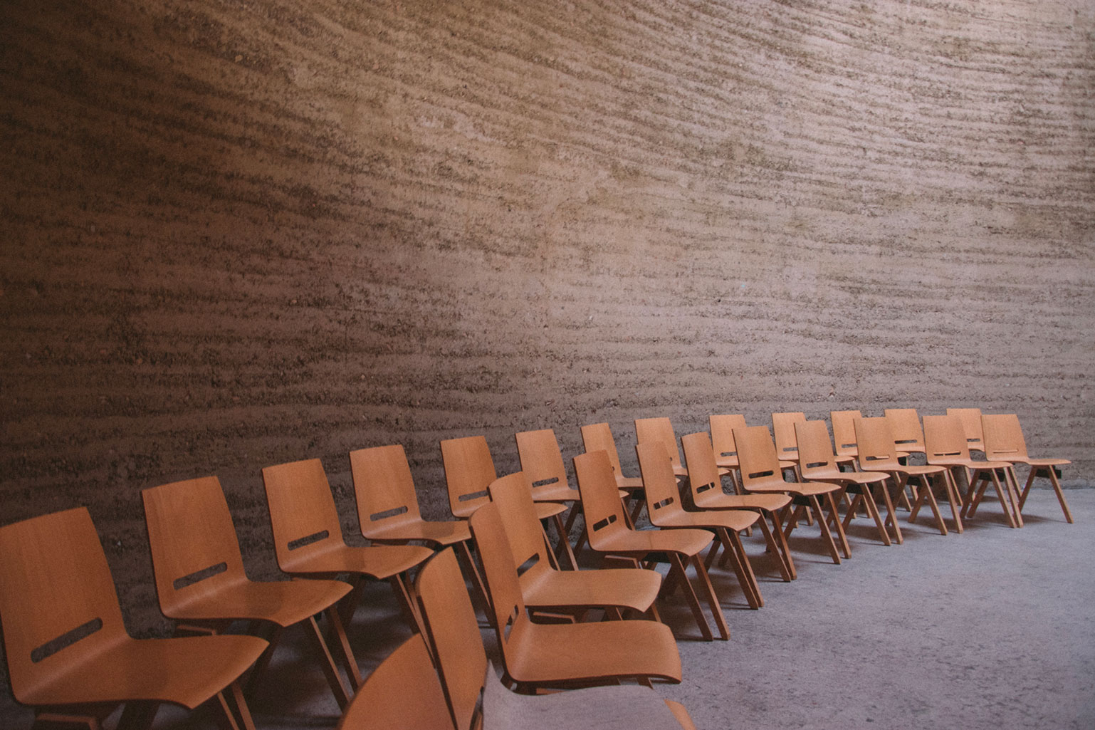 two rows of empty wooden chairs