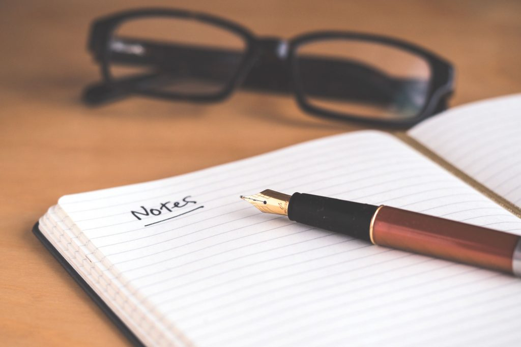 notepad with pen and glasses on table