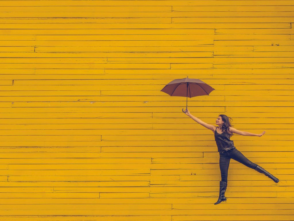 woman jumping with umbrella in hand