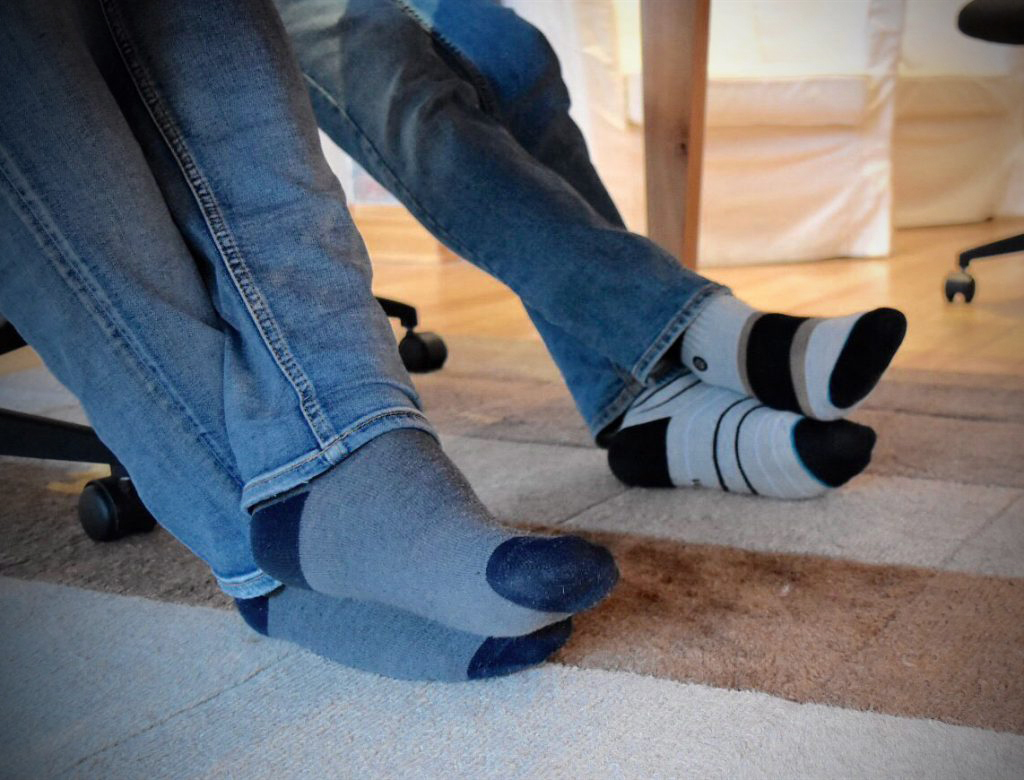 two pairs of feet under table in socks