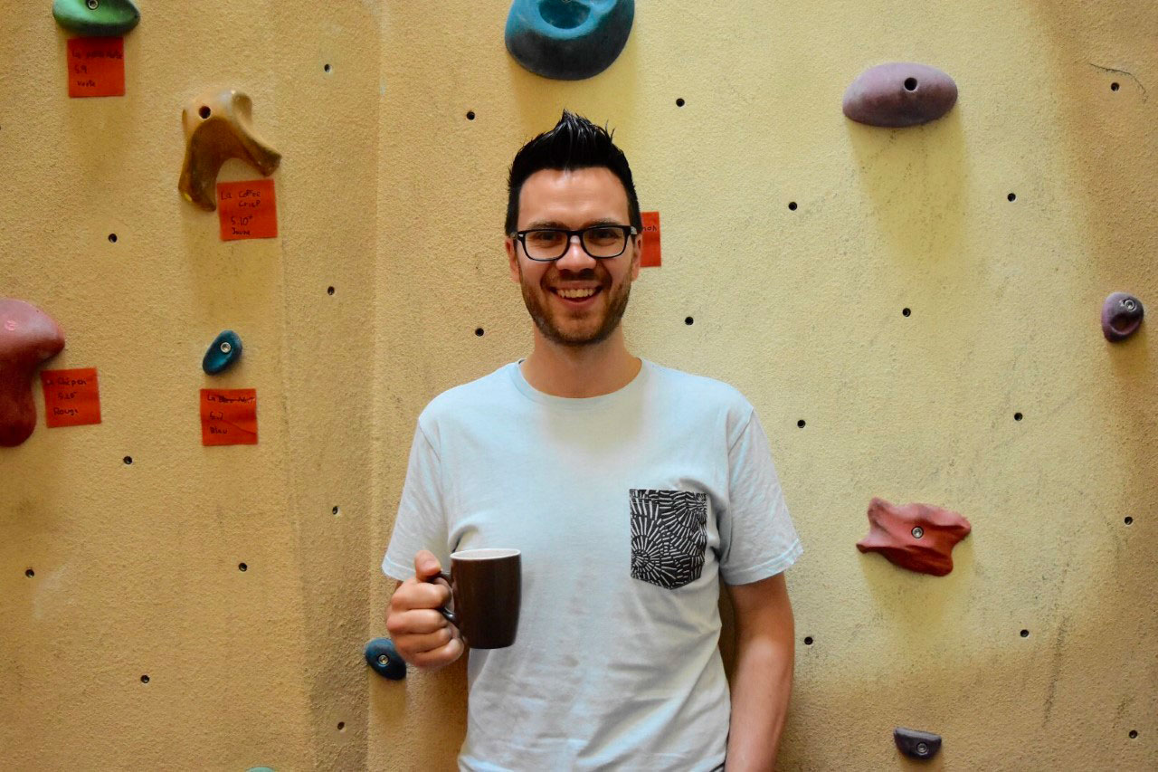 man standing in front of rock climbing wall with coffee mug
