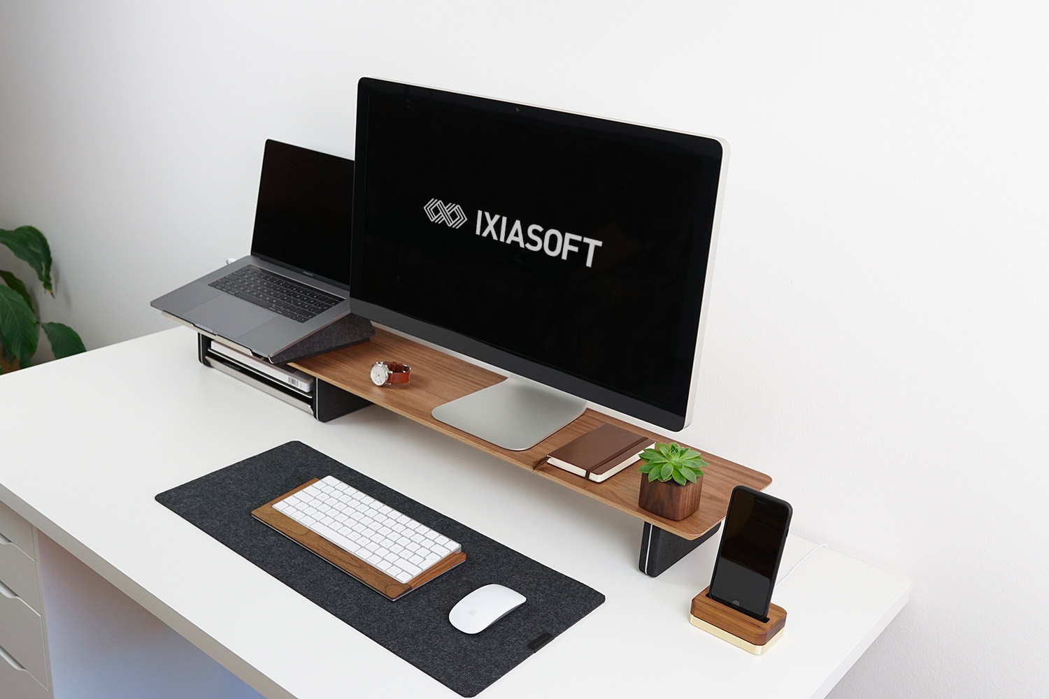 A desktop, laptop, and Iphone on a white desk.